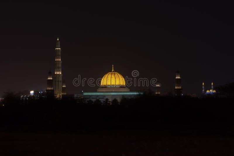 En bred sikt av Sultan Qaboos Grand Mosque och Al Ameen Mosque i Muscat, Oman på natten som visar av och glödande kupolfärger fotografering för bildbyråer