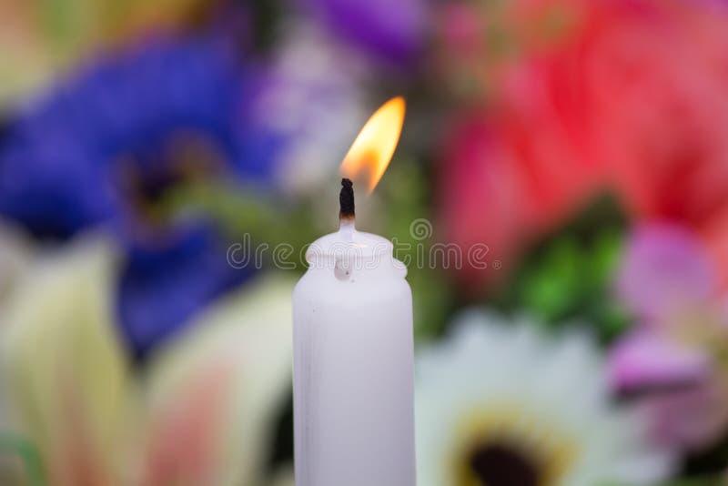 En brinnande gammal vit stearinljus på suddighetsbakgrund royaltyfri bild