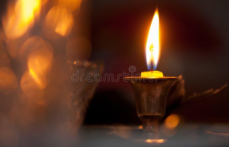 En brinnande stearinljus i en bronsljusstake på en festlig tabell med royaltyfri fotografi