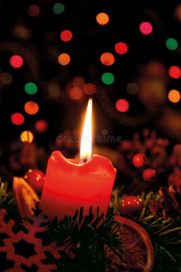 En brinnande stearinljus på en adventkrans på en bakgrund av en julgran royaltyfri bild