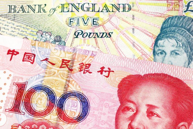 En brittisk fem pund anmärkning med en röd kinesisk yuan arkivbild