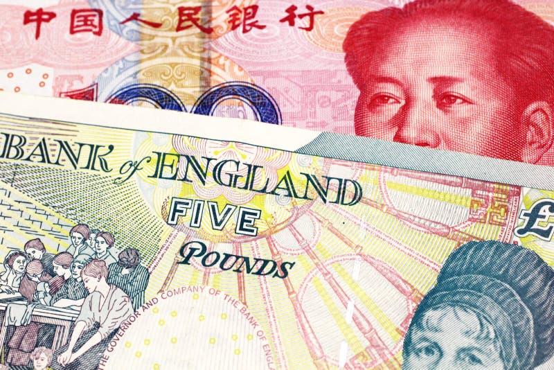 En brittisk fem pund anmärkning med en röd kinesisk yuan royaltyfria foton