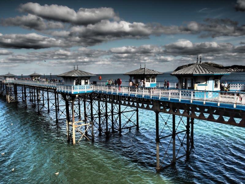 En bro med små hus som är högra på havet i ett trevligt färgrikt arkivfoton