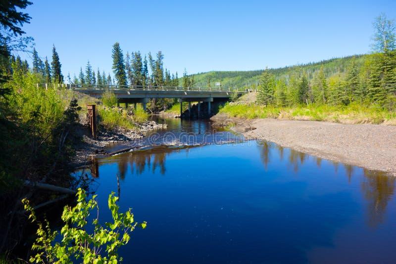 En bro som spänner över en flod på ett avlägset läge i alaska arkivfoto