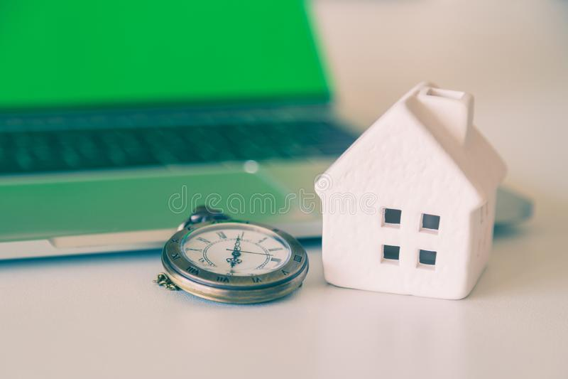 En bronsklockahalsband och ett vitt keramiskt hus med bärbar datorbakgrund fotografering för bildbyråer