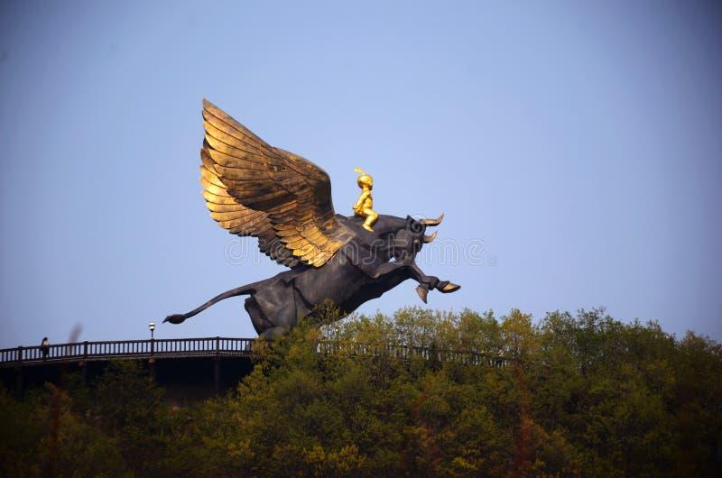 En bronstjur som tvättar sig upp i himlen royaltyfria bilder