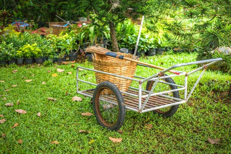 En Broon och en vide- korg på vagnen i trädgården arkivbild