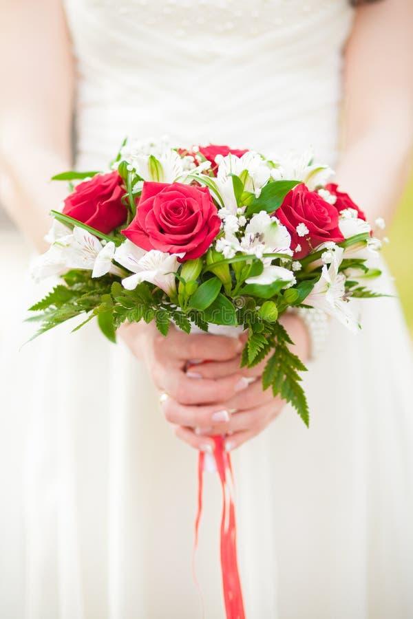 En brud- bukett av rosor i händer av bruden arkivbild