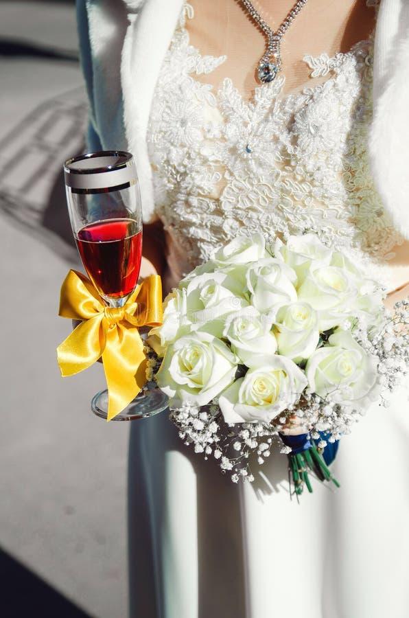 En brud i en bröllopsklänning rymmer en bukett av vita rosor och ett exponeringsglas av vin arkivfoto