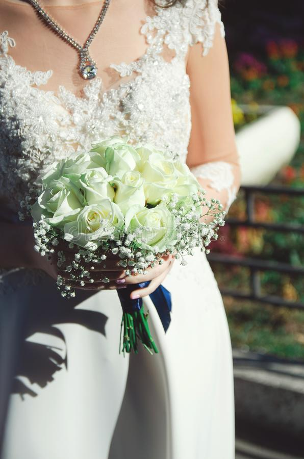 En brud i en härlig bröllopsklänning rymmer en bukett av vita rosor royaltyfri bild