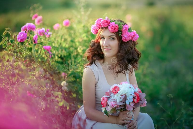 En brud i en vit klänning rymmer en bukett av rosor och callas på bakgrunden av grönt gräs arkivfoton