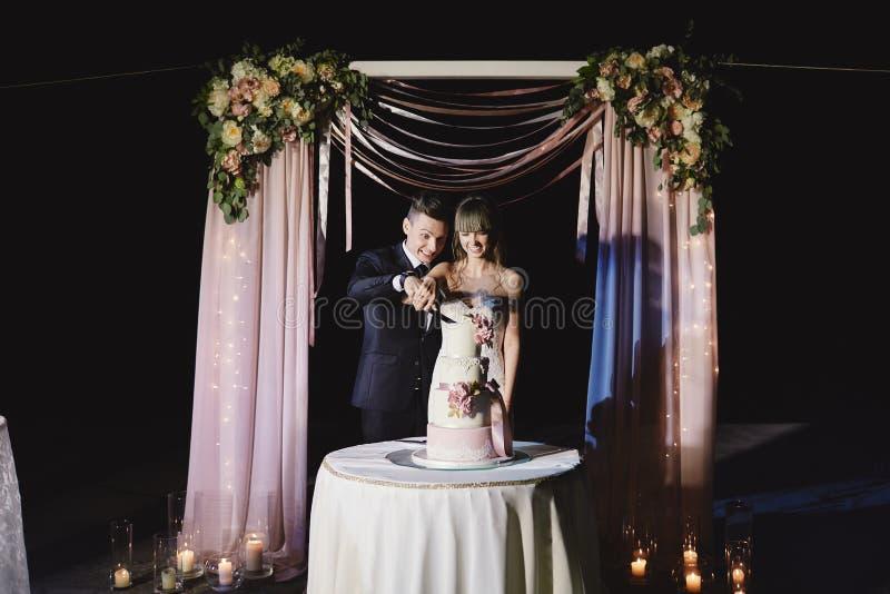 En brud och en brudgum klipper deras br?llopst?rta h?rlig cake nicelljus gifta sig f?r trappa f?r st?ende f?r brudbegreppskl?nnin royaltyfri fotografi