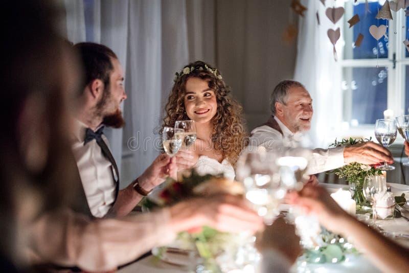 En brud och en brudgum som sitter på en tabell på ett bröllop som klirrar exponeringsglas arkivbilder