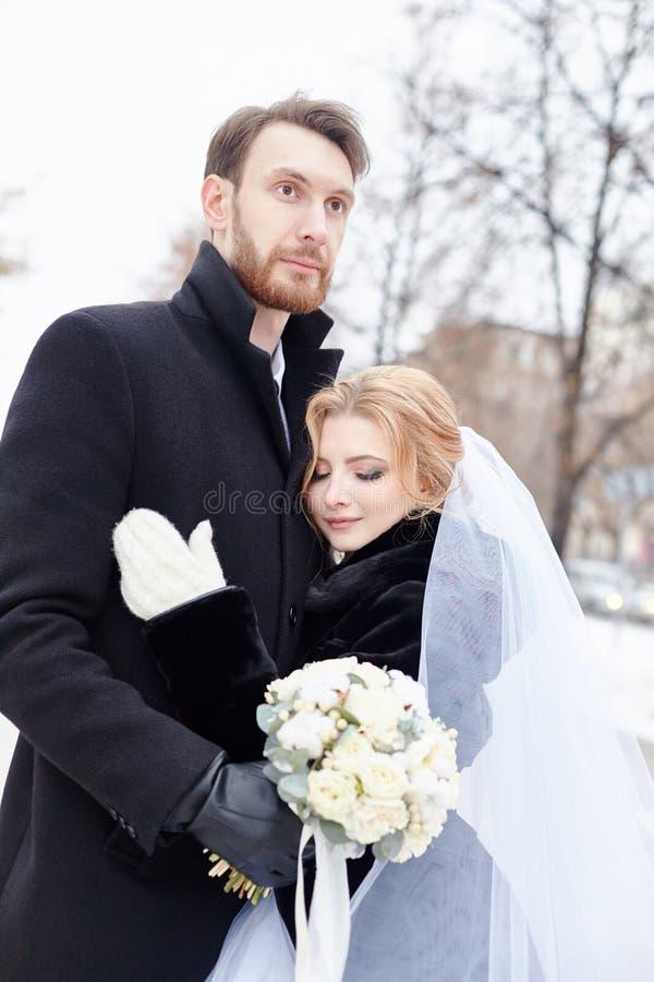 En bruid en bruidegom die terwijl status op de straat koesteren kussen royalty-vrije stock afbeelding