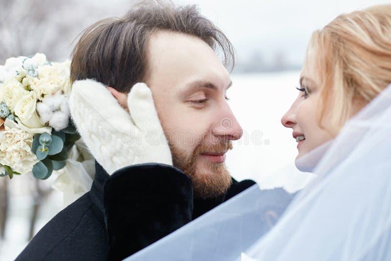 En bruid en bruidegom die terwijl status op de straat koesteren kussen royalty-vrije stock foto