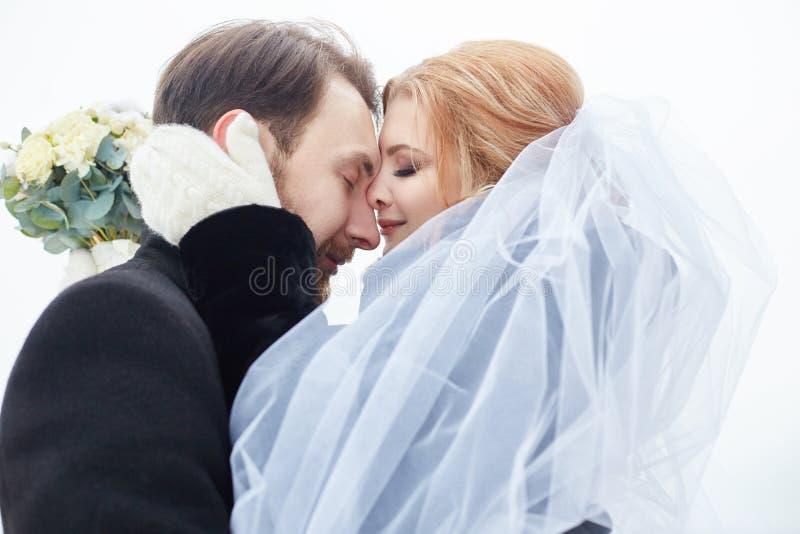 En bruid en bruidegom die terwijl status op de straat koesteren kussen stock foto's