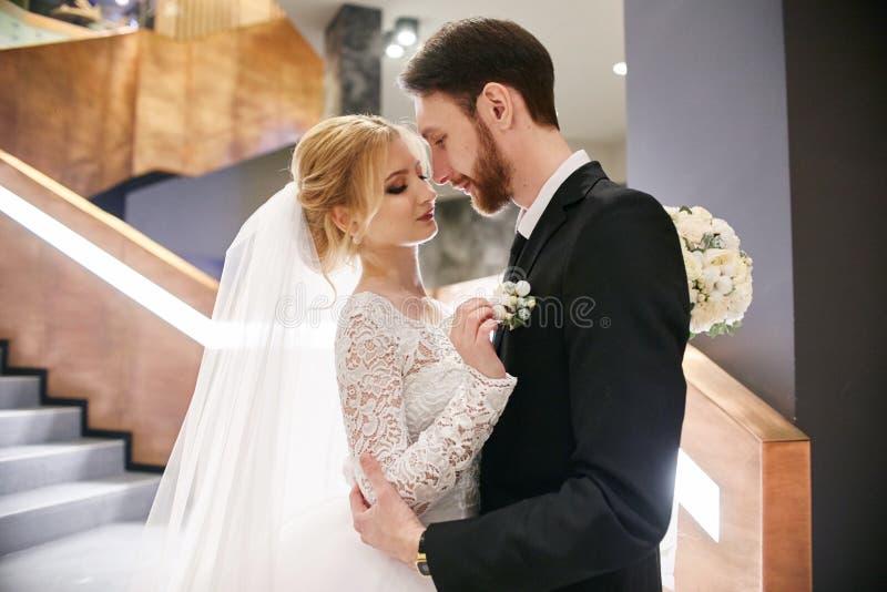 En bruid en bruidegom die terwijl status op de treden koesteren kussen stock afbeelding
