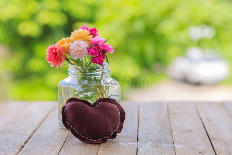 En brun kudde och mossa steg blommor i en glass krus på träta arkivfoton
