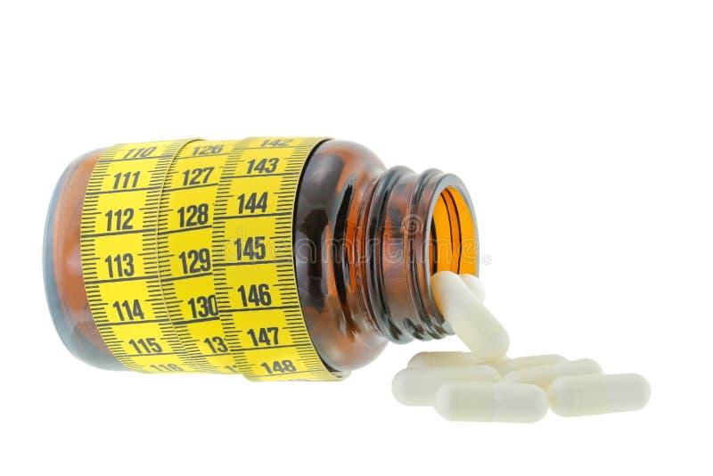 En brun medicinflaska med vita kapslar som ut faller royaltyfri fotografi