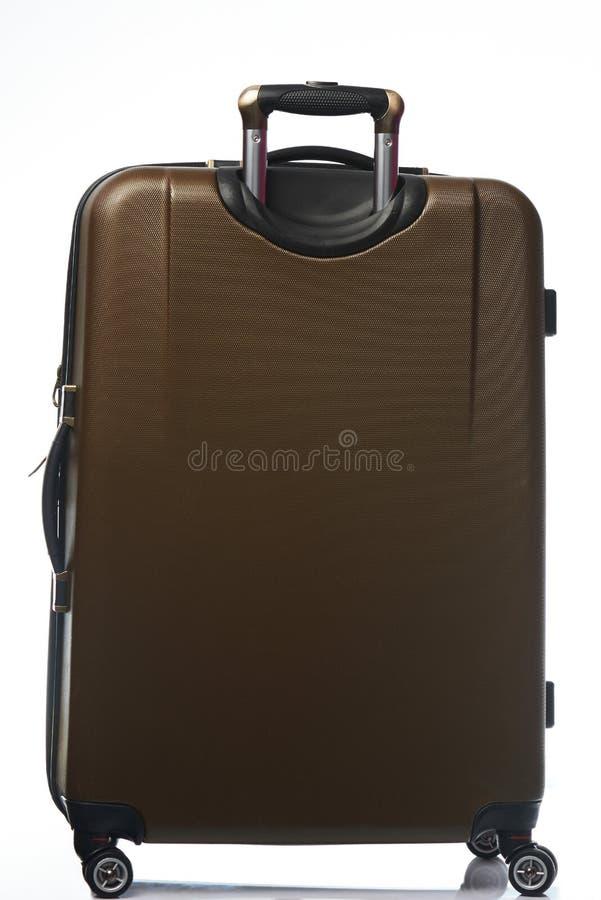 En brun plast- resväska royaltyfri fotografi