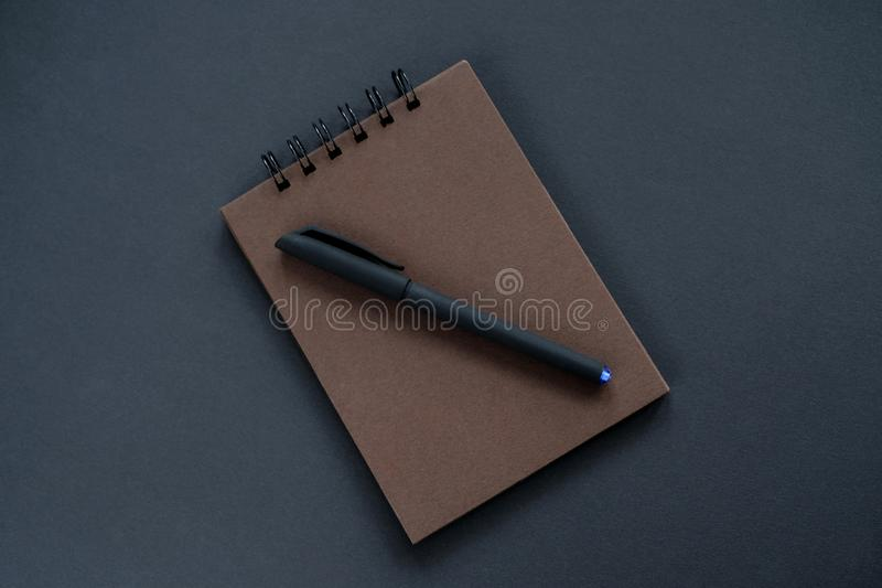 En brun sketchpad, en svart penna royaltyfria bilder