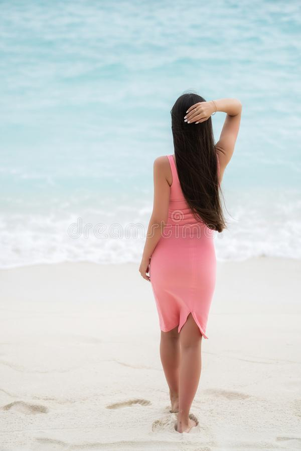 En brunett i en rosa passande klänning står med hennes baksida till kameran arkivfoton