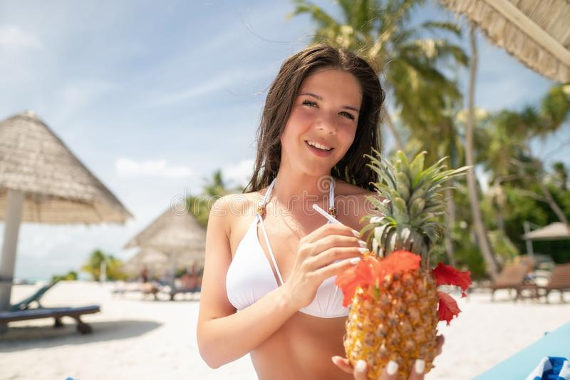 En brunett i en vit baddräkt sitter på en dagdrivare med en Pina Colada coctail i en ananas royaltyfri foto
