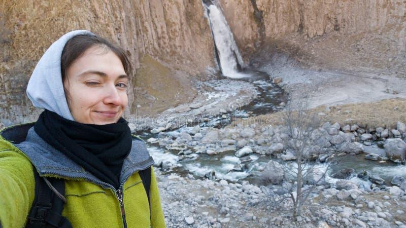 En brunettflicka blinkar mot bakgrund av en vattenfall Resor i kallt väder En flicka i en rock och en hoodie Höst eller vinter fotografering för bildbyråer