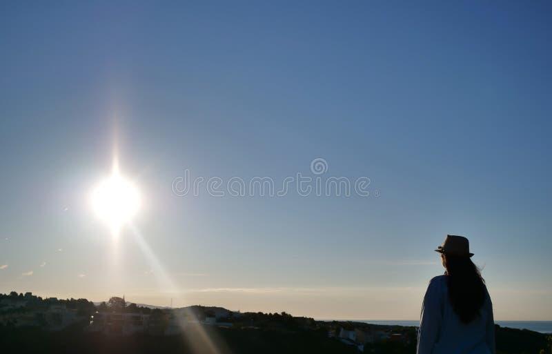 En brunettflicka med ett hattanseende mot himlen ser soluppgången, copyspace royaltyfri fotografi