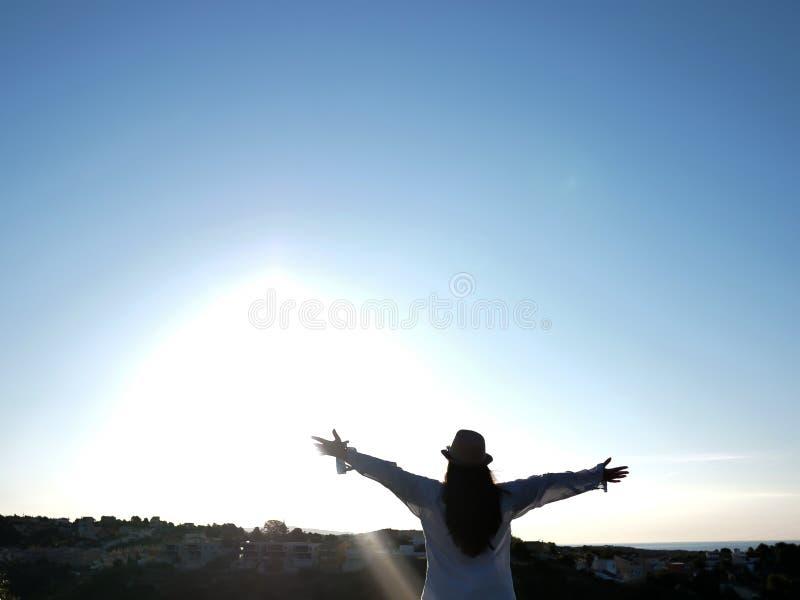 En brunettflicka med en hatt står mot himlen med hennes händer splined in mot solen, solens strålar arkivbild