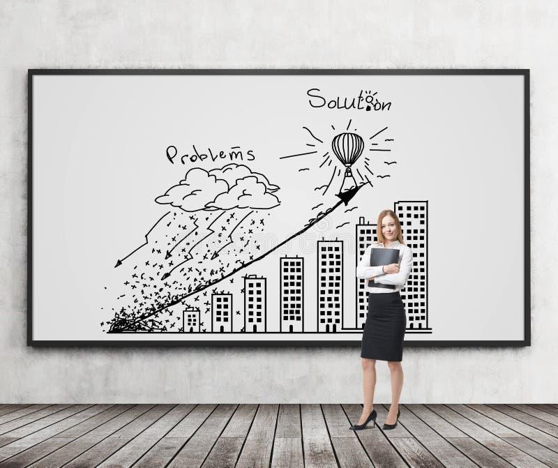 En brunettkvinna i formell kläder rymmer en svart mapp- och gåvors problem och lösnings' strategi med grafen på th arkivbild