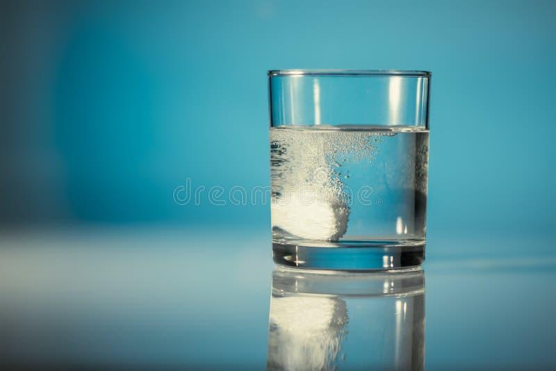 En brustablett i ett exponeringsglas av vatten royaltyfri foto