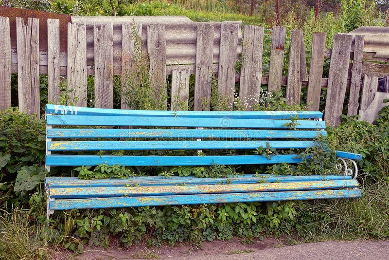 En bruten blå träbänk som är bevuxen med gräs nära ett grått staket arkivbild