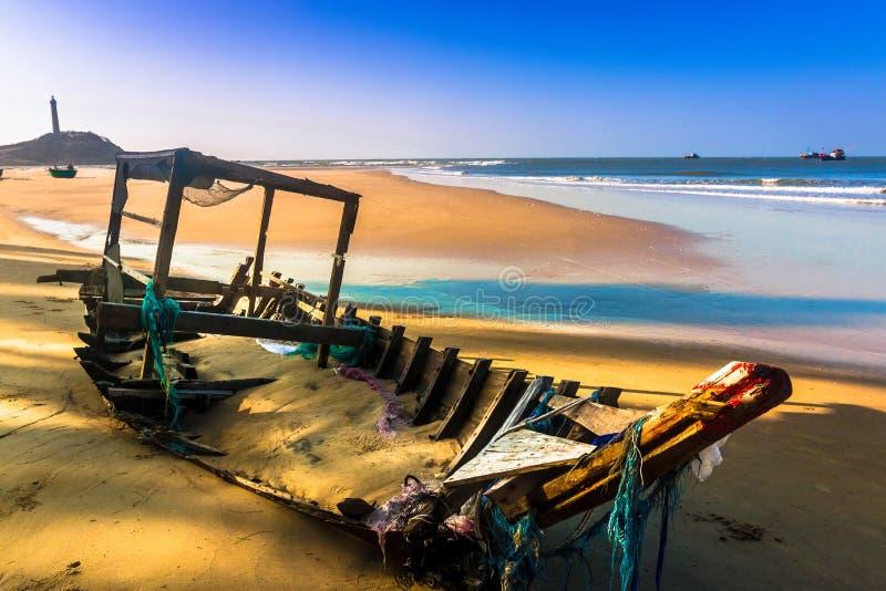 En bruten gammal fiskebåt på Sandy Beach på Ke-gummin udde, Binh Thuan, Vietnam arkivbilder
