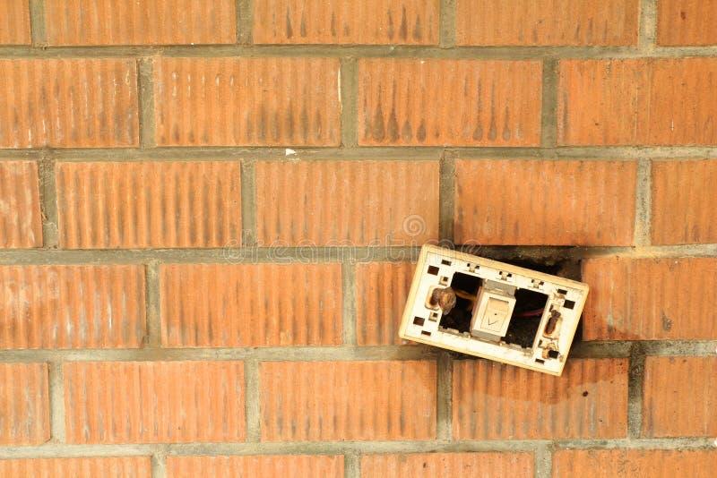 En bruten 'På/av' strömbrytare på den orange tegelstenväggen arkivfoton