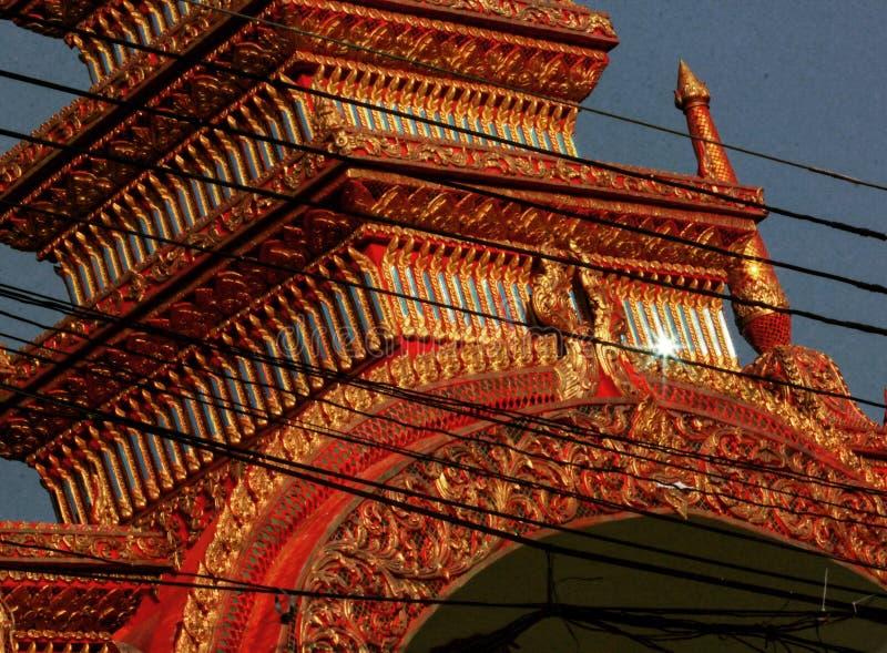 En buddistisk kloster i Thailand som fångas in bak kraftledningar och en tryckvåg av solsken arkivbilder