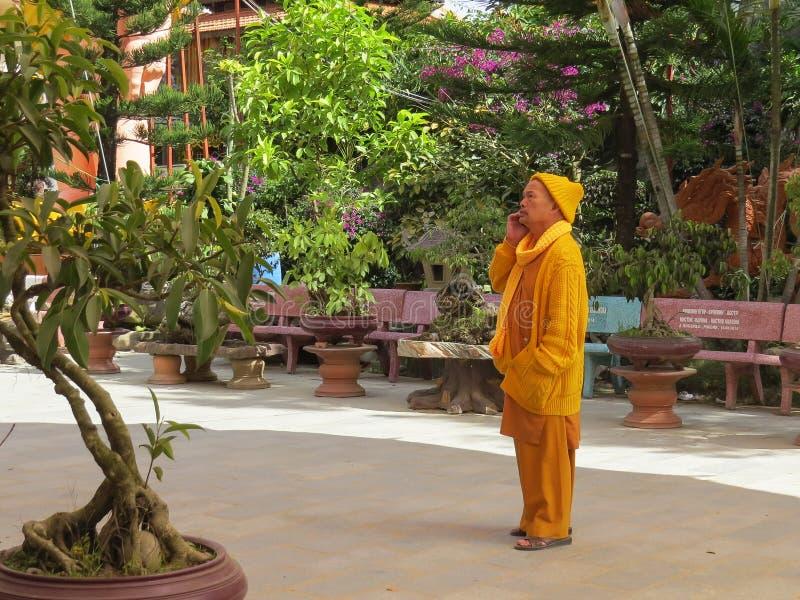 En buddistisk munk i gul kläder lyssnar till något på en mobiltelefon på gränden som leder till templet av det guld- royaltyfri bild