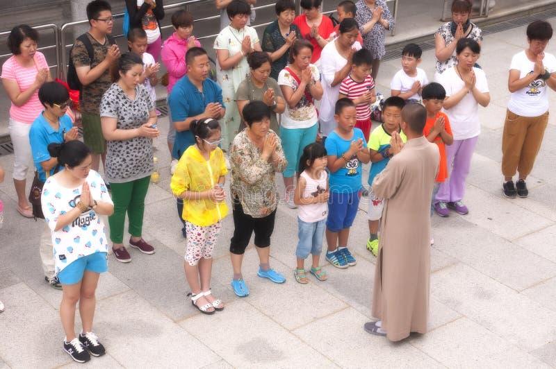 En buddistisk munk Leading Prayer