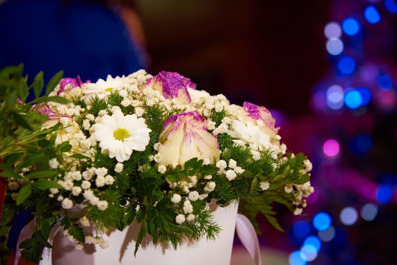 En bukett av blommor i en ask på bakgrunden av ljus mång--färgad bokeh royaltyfri foto