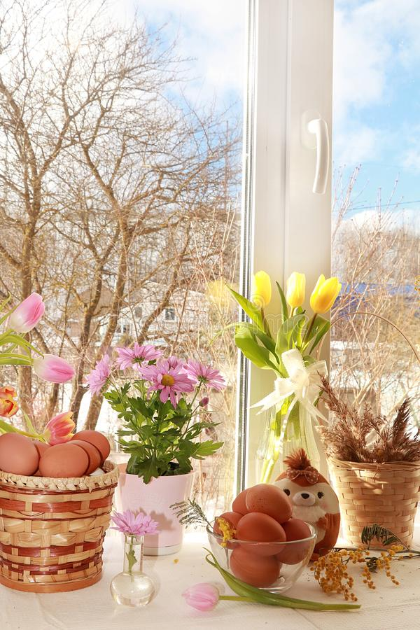 En bukett av blommor och en korg med ägg på ett lantligt fönster, förberedelse för påsk arkivbilder