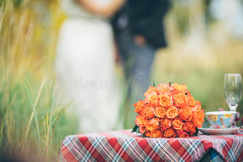En bukett av blommor på en uppsättningbrölloptabell med en brud och en gro arkivbild
