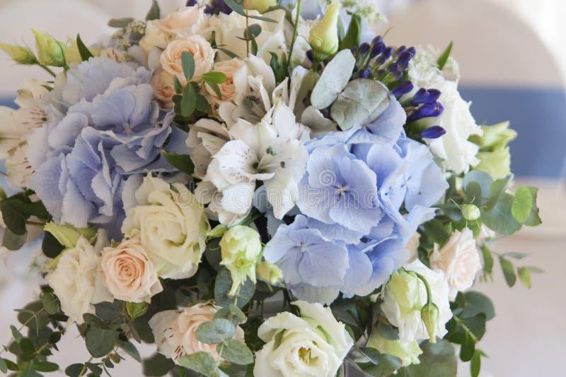 En bukett av blommor på en vit ställning på ferietabellen Vit bordduk på tabellen royaltyfri fotografi