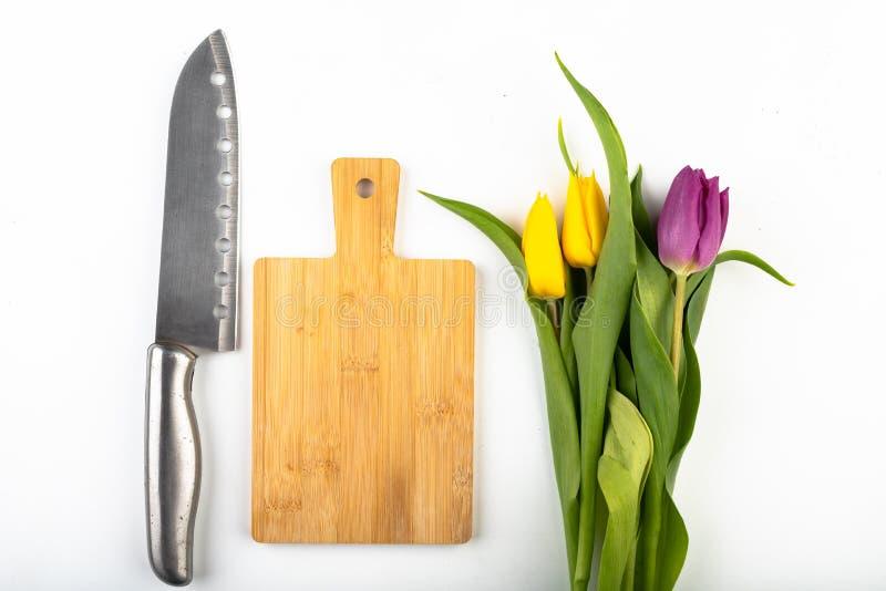 En bukett av blommor p? k?ksbordet Tr?sk?rbr?da, kniv och kvass arkivbild