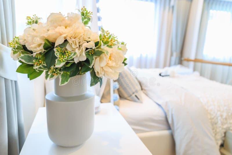En bukett av den konstgjorda blomman i en kruka med säng och rullgardiner tillbaka royaltyfria foton