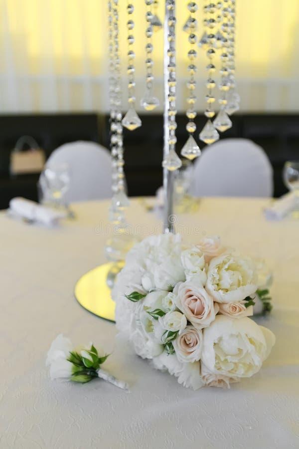 En bukett av en brud från vita rosor och pioner och en lögn för boutonniere för brudgum` s på en dekorerad tabell royaltyfri bild