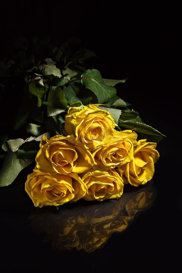 En bukett av gula rosor med små droppar på en mörk bakgrund arkivfoto
