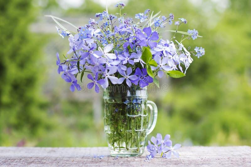 En bukett av härliga blåa blommor mot gör grön trädgården royaltyfri bild