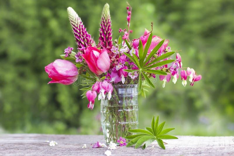 En bukett av härliga blommor av rött på gör grön trädgårds- backgrou royaltyfri bild