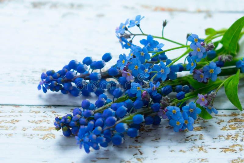 En bukett av musary och små blåa blommor på en ljus bakgrund fotografering för bildbyråer