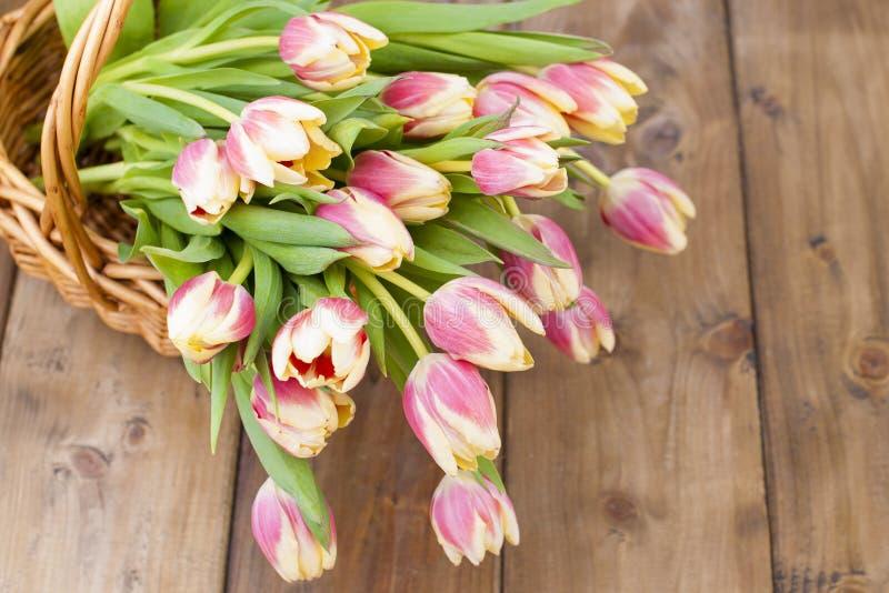 En bukett av nya vårtulpan, av olika färger Blommor i en korg på en brun träbakgrund Fritt utrymme för text eller a arkivbilder